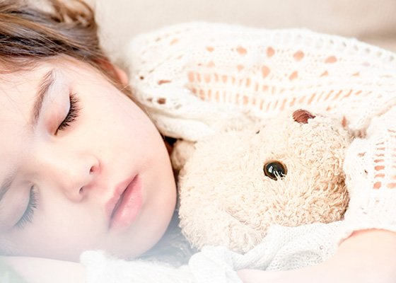 Kind mit Teddy-Bär im Bett