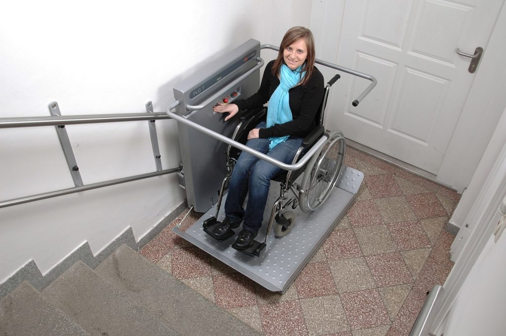 Junge Frau im Rollstuhl im Treppenlifter