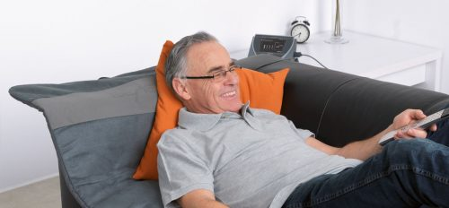 Älterer Mann liegt auf Couch