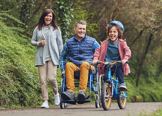 Frau mit Mann im Rollstuhl, Kind auf dem Fahrrad
