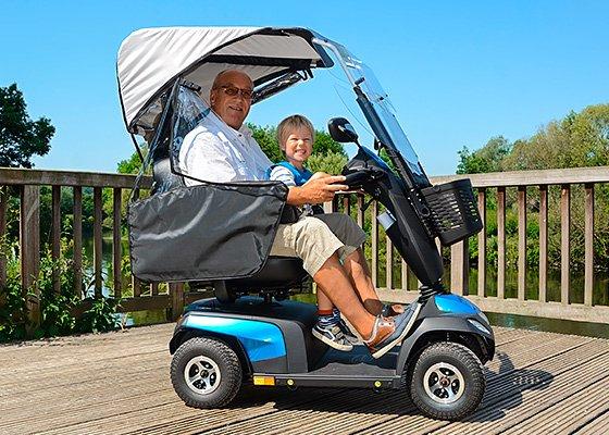 Mann mit Enkel im Elektromobil