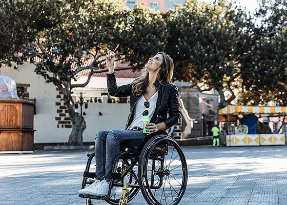 Frau in Rollstuhl macht Seifenblasen