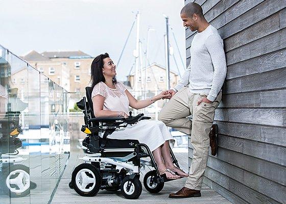 Junge Frau im Rollstuhl unterhält sich mit Mann