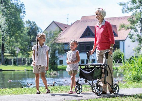 Senior mit Rollator mit Enkeln im Garten