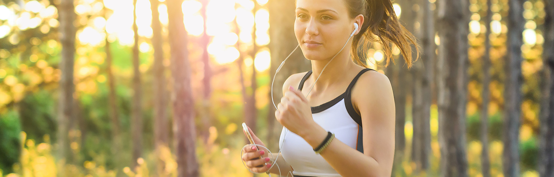 Junge Frau mit Kopfhörern beim Joggen