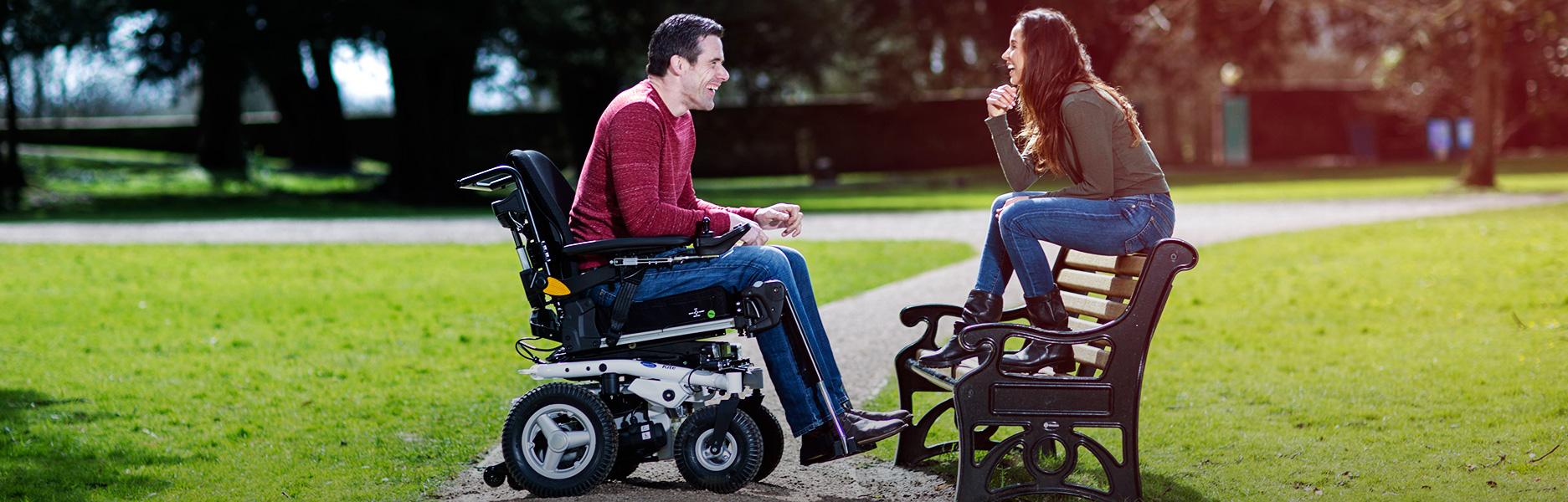 Mann im Elektrorollstuhl unterhält sich mit Frau auf Parkbank