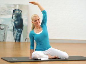 Sitzende junge Frau macht Übungen auf Yoga-Matte