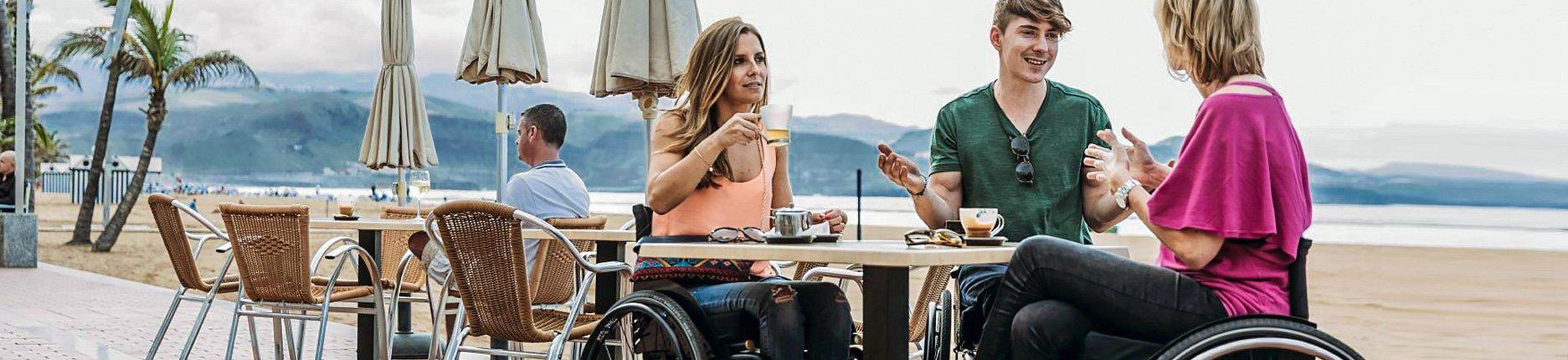 Junge Menschen im Rollstuhl unterhalten sich auf Café-Terasse