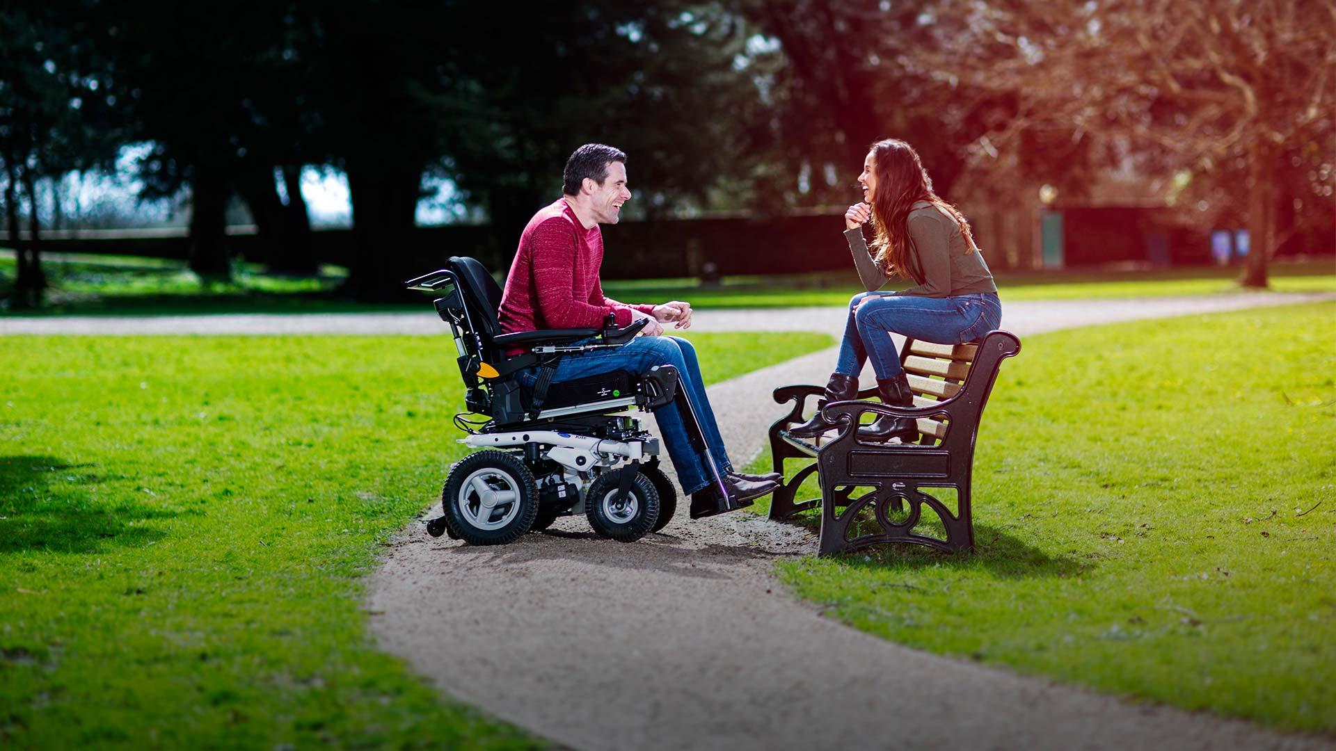 Mann mit Elekrorollstuhl unterhält sich mit Frau auf Parkbank