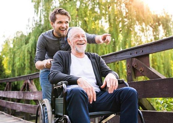 Junger Mann schiebt Senior im Rollstuhl