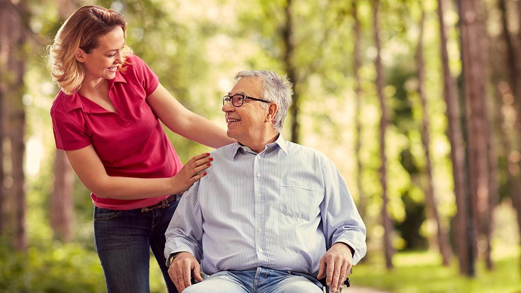 Junge Frau schiebt lächelnden Mann im Rollstuhl im Wald