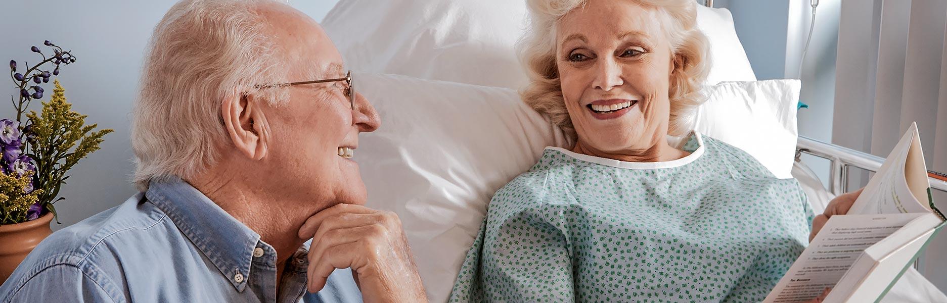 Lachendes älteres Ehepaar, Frau liegt im Pflegebett