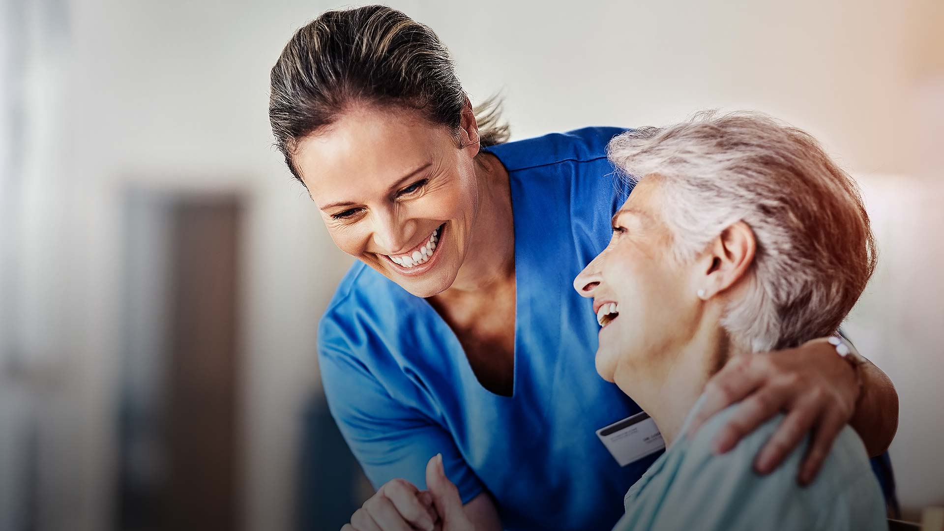 Lachende Pflegerin mit lachender Seniorin