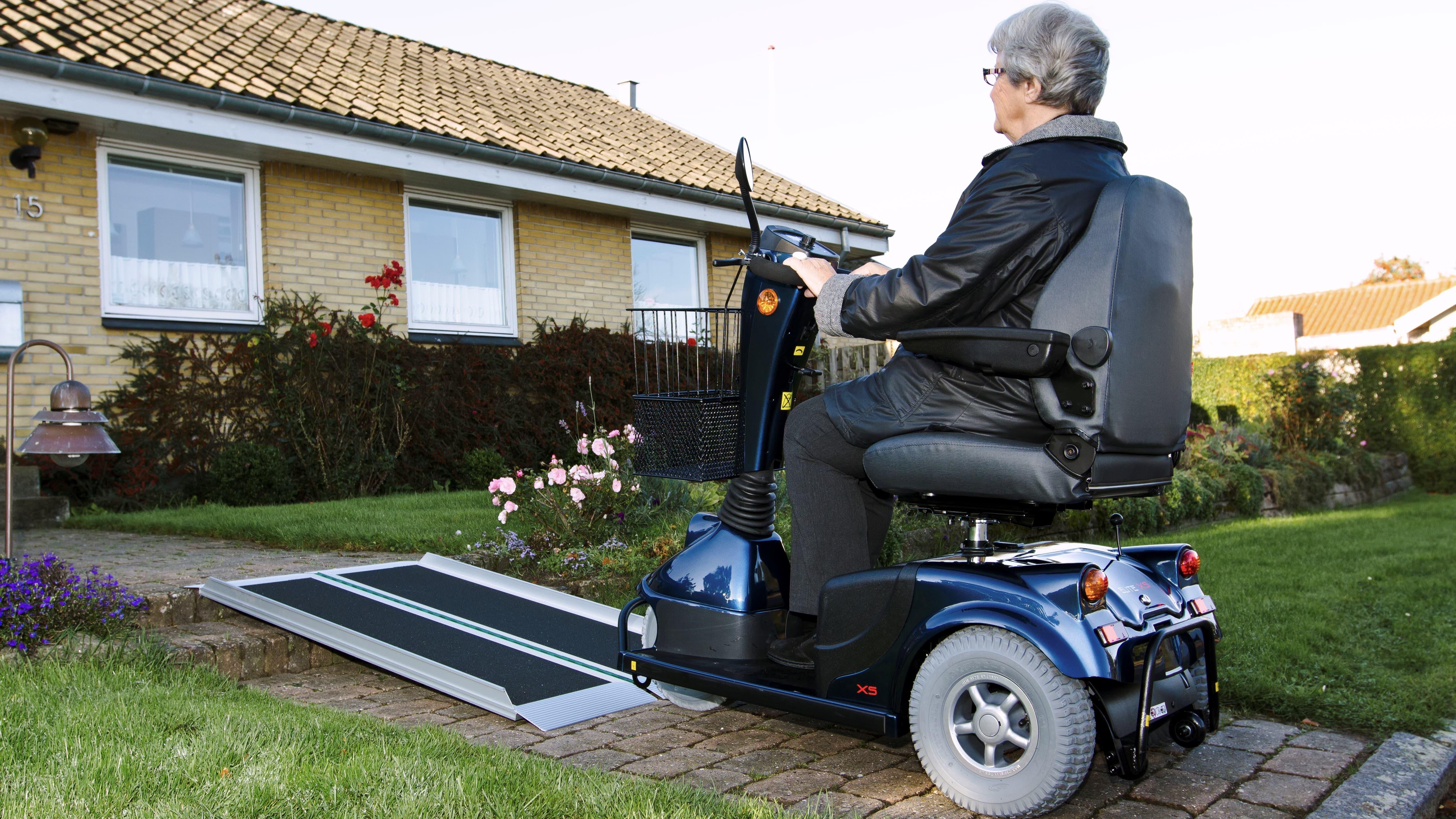 Ältere Frau mit Elektrorollstuhl auf Rampe